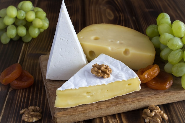 Różne rodzaje sera, winogron i suszonych moreli na brązowej desce do krojenia