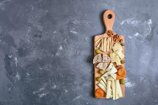Różne rodzaje serów, suszone morele, pieczywo pełnoziarniste, orzechy, oliwki, kapary na desce.
