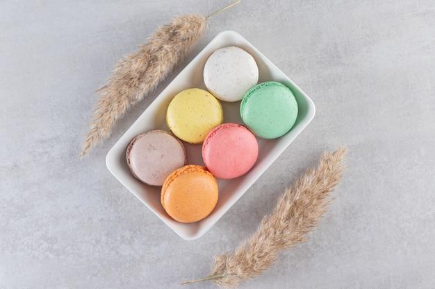 Różne rodzaje słodkich ciastek migdałowych w białej misce na kamiennej powierzchni