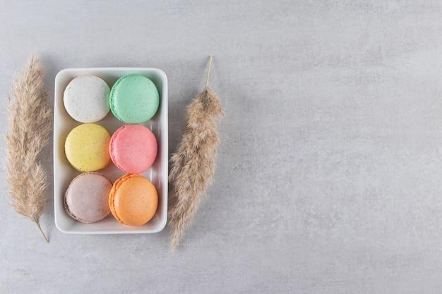 Różne rodzaje słodkich ciastek migdałowych w białej misce na kamiennym tle.