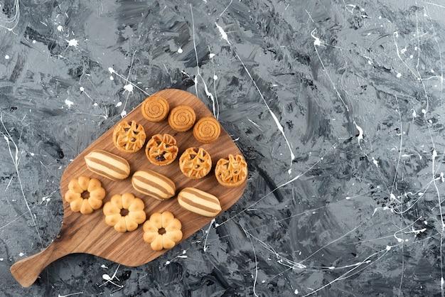 Różne rodzaje słodkich wypieków na drewnianej desce do krojenia