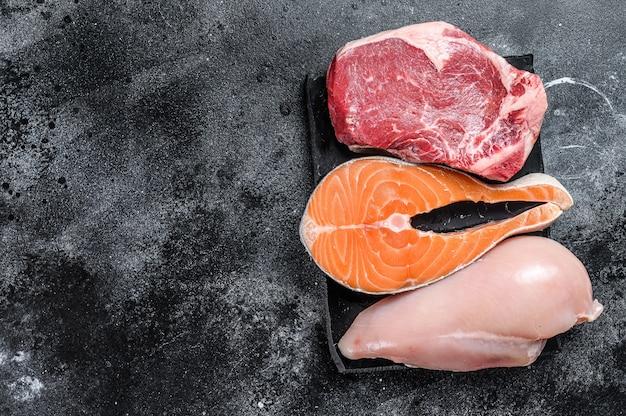 Różne rodzaje steków z surowego mięsa rostbef wołowy, łosoś i pierś z kurczaka