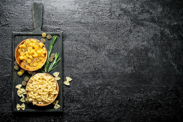Różne rodzaje surowego makaronu w miseczkach z rozmarynem. na czarnym tle rustykalnym