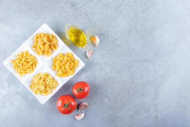 Różne rodzaje surowego suchego makaronu ze świeżymi czerwonymi pomidorami i olejem na kamiennym tle.