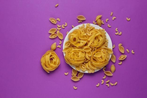 Różne rodzaje surowego włoskiego makaronu w talerzu na fioletowym tle. widok z góry.