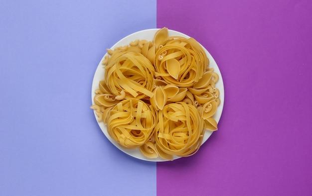 Różne rodzaje surowego włoskiego makaronu w talerzu na fioletowym tle.