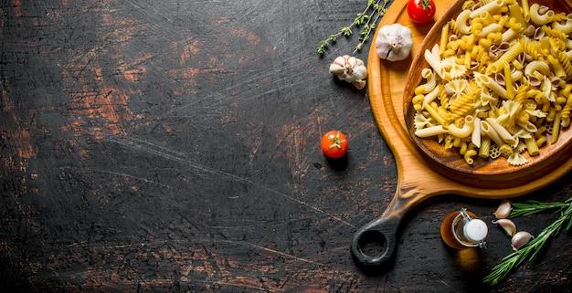 Różne rodzaje surowej pasty na talerzu z tymiankiem, czosnkiem i oliwą w butelce.