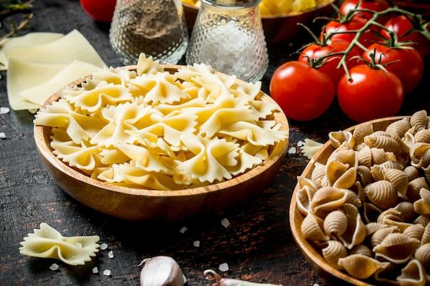Różne rodzaje surowej pasty w miseczkach z czosnkiem, pomidorami i przyprawami. na tle rustykalnym
