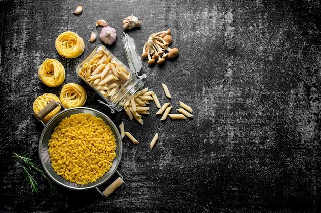 Różne rodzaje surowej pasty w słoiku oraz durszlak z grzybami i czosnkiem. na tle rustykalnym