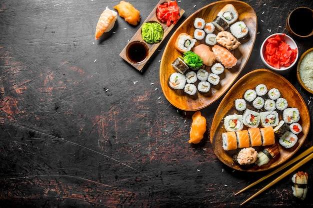 Różne rodzaje sushi, bułek i maki na talerzach. na ciemnym rustykalnym stole