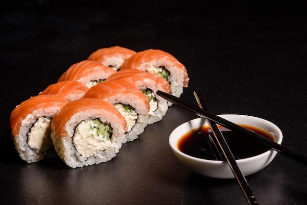 Różne rodzaje sushi podawane w ciemności. bułka z łososiem, awokado, ogórkiem. menu sushi. japońskie jedzenie.