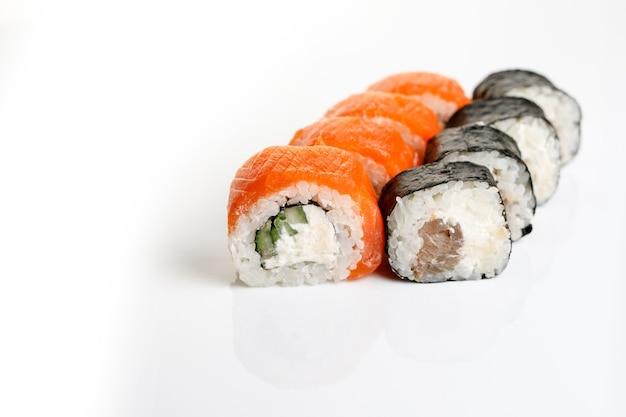 Różne rodzaje sushi serwowane na na białym tle.