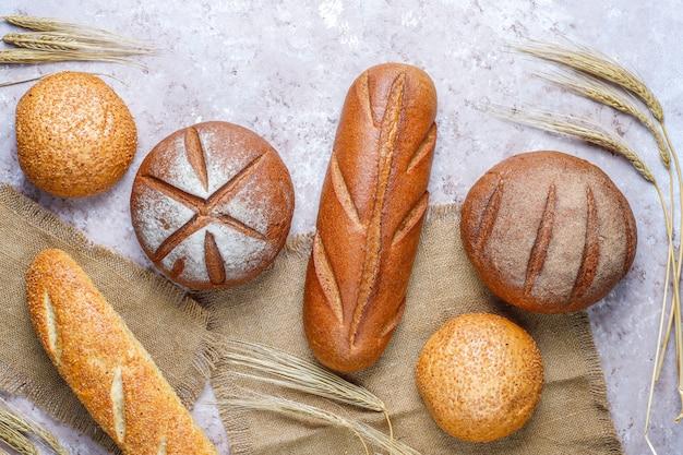 Różne rodzaje świeżego chleba jako tło, widok z góry