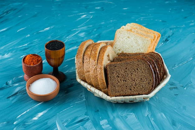 Różne rodzaje świeżego chleba w koszu z solą i pieprzem na jasnym tle.