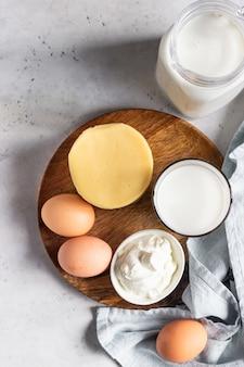 Różne rodzaje świeżych produktów mlecznych i jaj na drewnianym talerzu. naturalne produkty rolne.