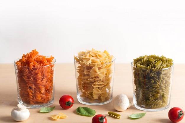 Różne rodzaje włoskiego makaronu z warzywami na stole