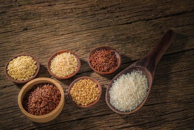 Różne rodzaje ziaren zbóż (pszenica, ryż, ryż brązowy, kasza gryczana, jęczmień, czarny sezam, proso, nasiona lotosu, łzy hioba) różne surowe surowe ziarna na tle drewna.