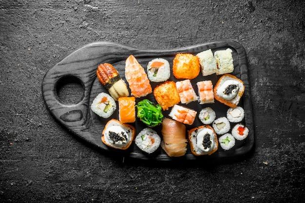 Różne rolki sushi na desce do krojenia. na czarnym rustykalnym stole
