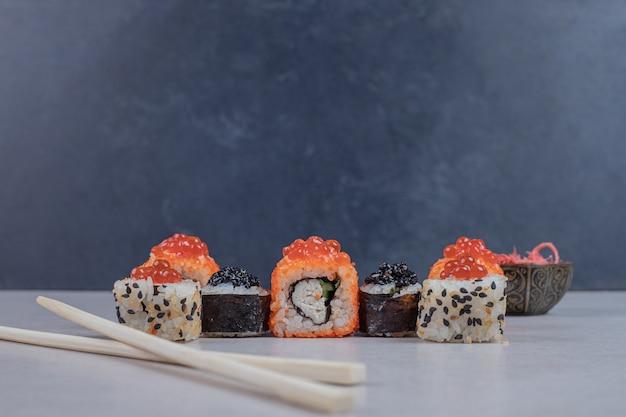 Różne rolki sushi ozdobione czerwonym kawiorem i pałeczkami.