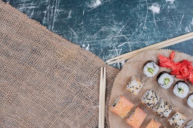 Różne rolki sushi podawane na drewnianym talerzu z marynowanym imbirem i pałeczkami.