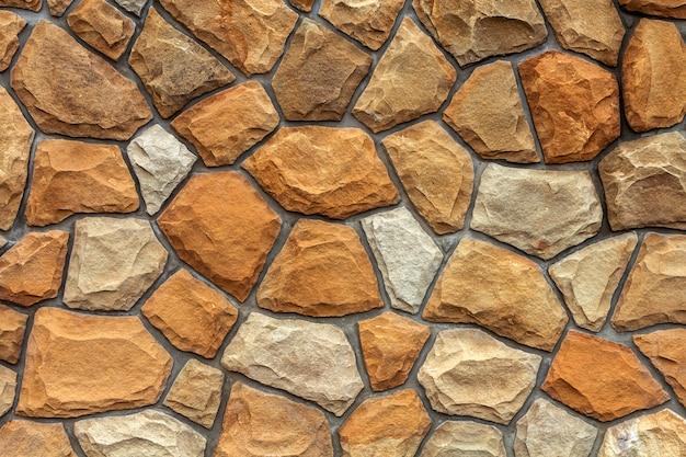 Różne rozmiary kamieni piaskowych. tle kamiennego muru