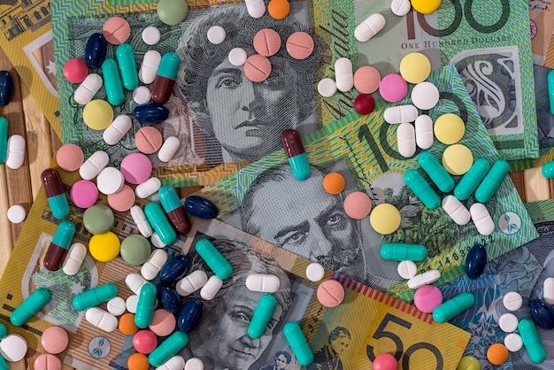 Różne rozproszone pigułki na banknotach dolara australijskiego