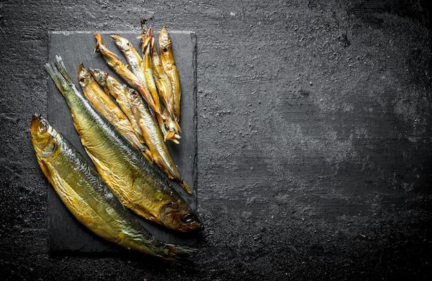 Różne ryby wędzone na kamiennej desce. na czarnym rustykalnym