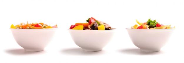 Różne sałatki warzywne na talerzach.