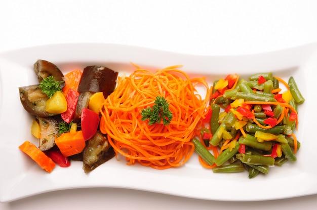 Różne sałatki warzywne na talerzu.
