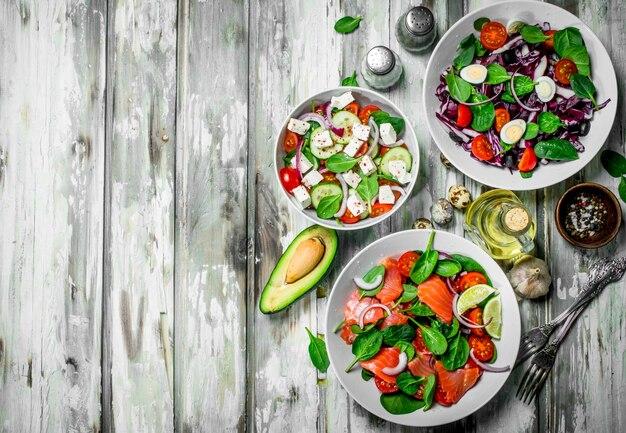 Różne sałatki z ekologicznych warzyw, ryb i serów z oliwą z oliwek i przyprawami. na rustykalnym tle.