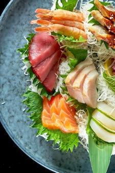 Różne sashimi z łososia, krewetki, tuńczyka, ośmiornicy, przegrzebka i węgorza. klasyczna kuchnia japońska. dostawa jedzenia. pojedynczo na czarno