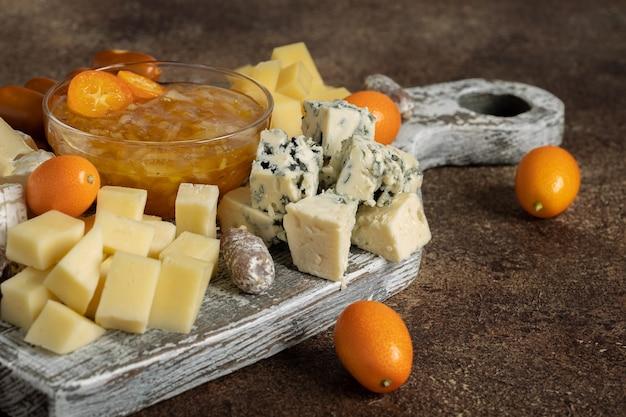 Różne sery i owoce kumkwatu na starej drewnianej desce na drewnianym stole