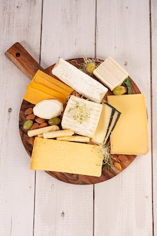 Różne sery na desce na drewnianym stole