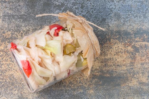Różne sfermentowane warzywa w przewróconym słoiku.