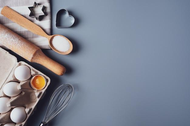 Różne składniki i przybory kuchenne do robienia ciasteczek lub babeczek, płasko świecki, copyspace. jajka, wałek do ciasta, trzepaczka, mąka, foremki do ciastek, układ na szarym tle. pojęcie domowego wypieku.