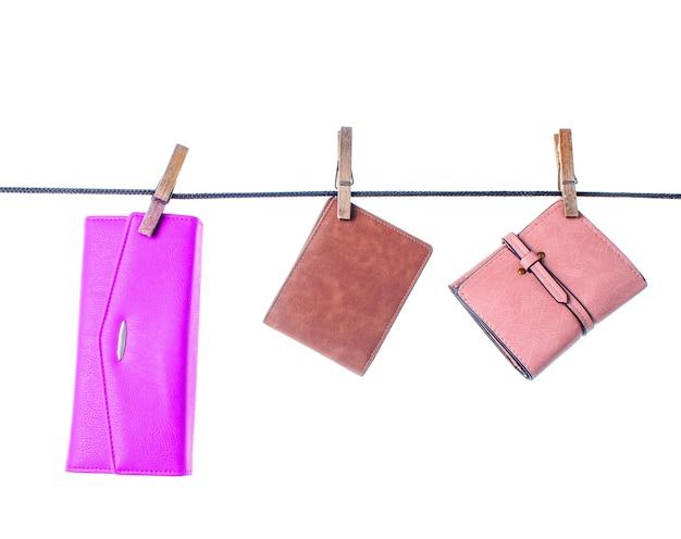 Różne skórzane portfele wiszą na sznurku z klamrami. izolowane
