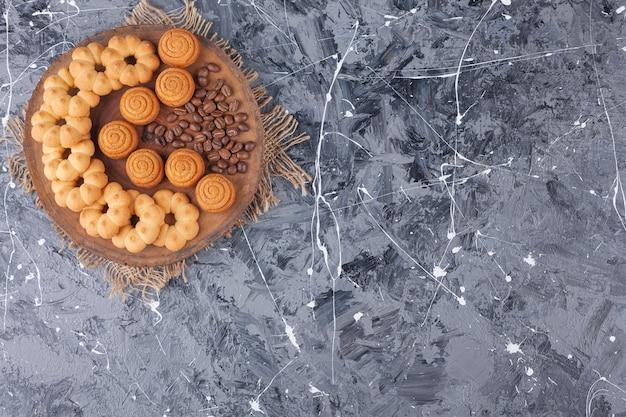 Różne słodkie ciasteczka z aromatem ziaren kawy na drewnianym kawałku.