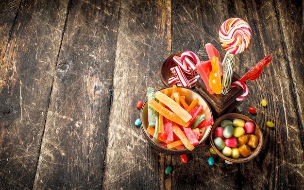Różne słodkie cukierki w miseczkach. na drewnianym tle.
