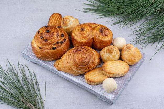 Różne słodkie wypieki i bułki z ciasteczkami na desce. zdjęcie wysokiej jakości