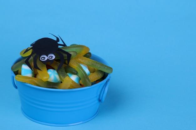 Różne słodycze, czekoladki i robaki w wiadrze. koncepcja wakacji na halloween