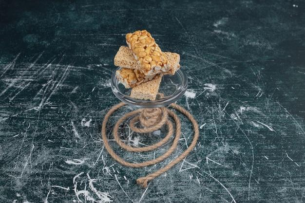 Różne słodycze kozinaki na szklanej misce ze sznurkiem.