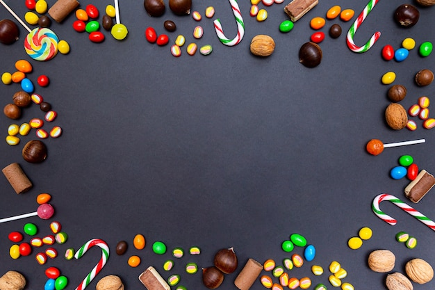 Różne słodycze, lizaki, cukierki, marmolada, orzechy włoskie, kasztany na czarnym tle.
