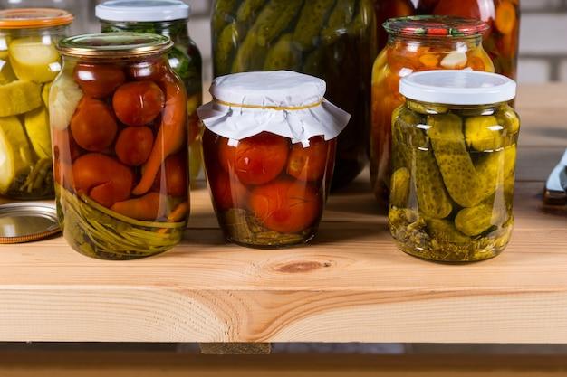 Różne słoiki marynowanych warzyw na drewnianym stole, wybór warzyw konserwowych na sprzedaż na targu rolniczym