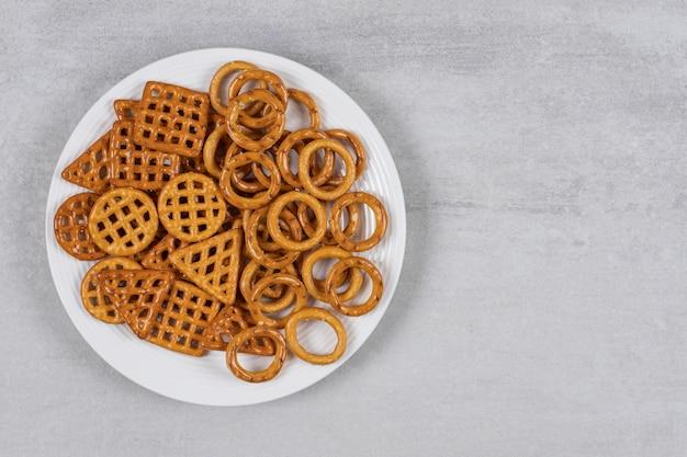 Różne słone krakersy na białym talerzu.