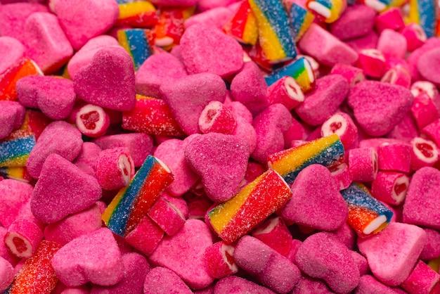 Różne smaczne cukierki gumowate. widok z góry. różowy galaretki słodycze tło.