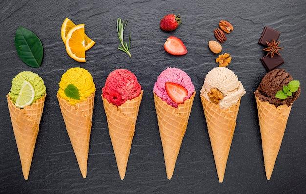 Różne smaki lodów w szyszkach ustawionych na ciemnym kamieniu