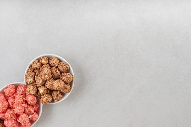 Różne smaki popcornu w małym talerzu z przekąskami na marmurowym stole.