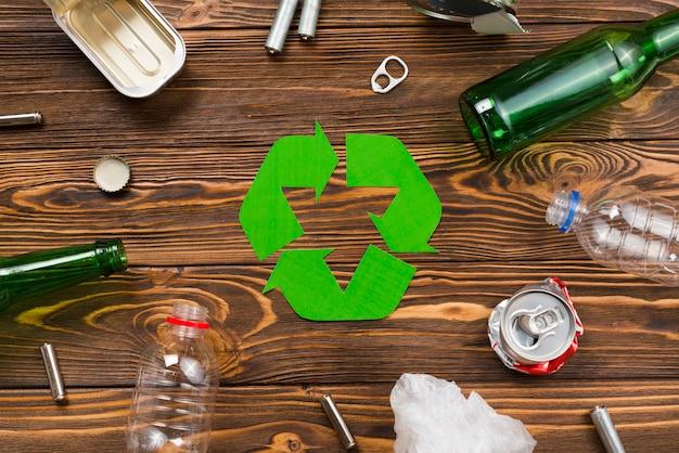 Różne śmieci wielokrotnego użytku wokół symbolu recyklingu