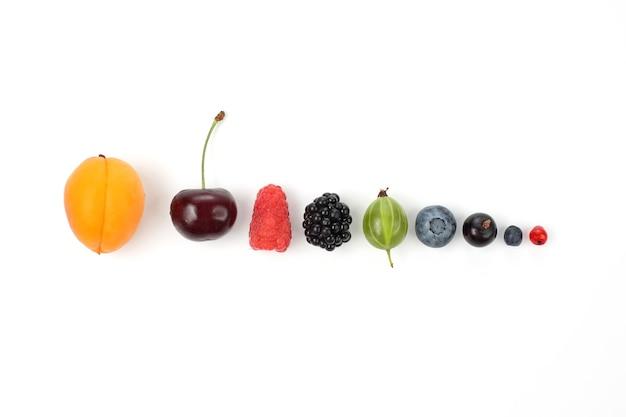 Różne soczyste jagody ułożone w rzędzie na białym tle