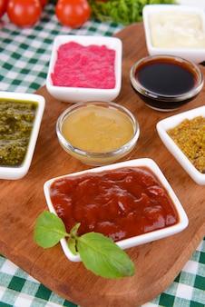 Różne sosy na desce do krojenia na stole z bliska